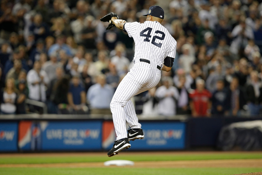 . New York Yankees relief pitcher Mariano Rivera (42) makes a leaping catch on a ball hit by Tampa Bay Rays\' Jose Lobaton in the ninth inning of a baseball game at Yankee Stadium, Thursday, Sept. 26, 2013, in New York. Lobaton was out at first. (AP Photo/Kathy Willens)