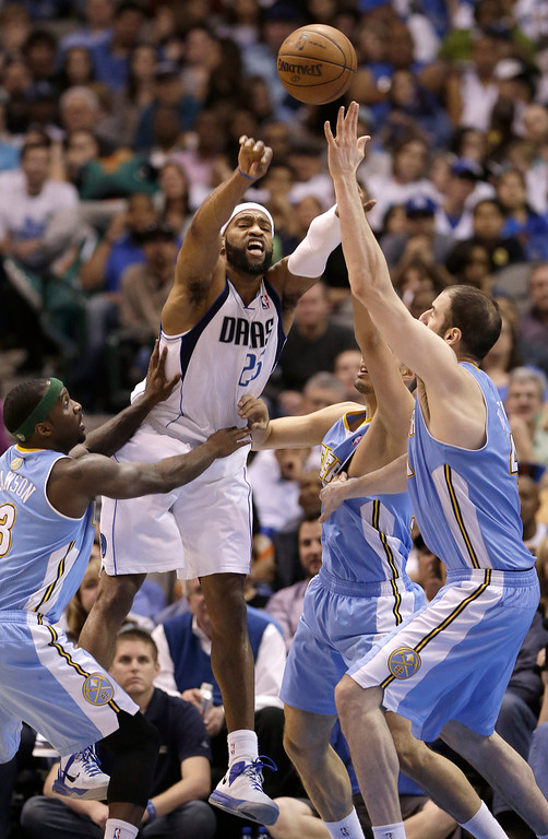. Dallas Mavericks shooting guard Vince Carter (25) passes against Denver Nuggets Corey Brewer (13), Evan Fournier, second from right, and Timofey Mozgov (25) during the first half of an NBA basketball game on Friday, April 12, 2013, in Dallas. (AP Photo/LM Otero)