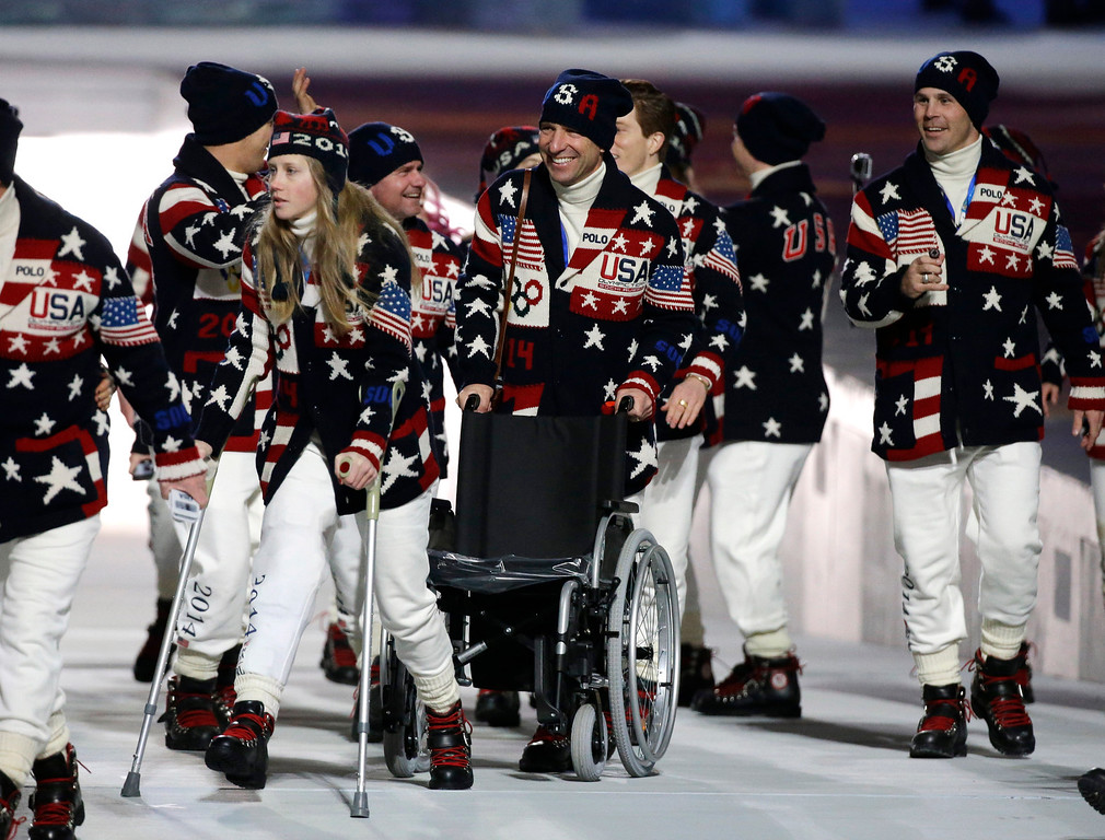 . Freeskier Heidi Kloser of the United States, left, walks on crutches after she injured her right leg during a training run before moguls qualifying as she arrives for the opening ceremony of the 2014 Winter Olympics in Sochi, Russia, Friday, Feb. 7, 2014. (AP Photo/Mark Humphrey)