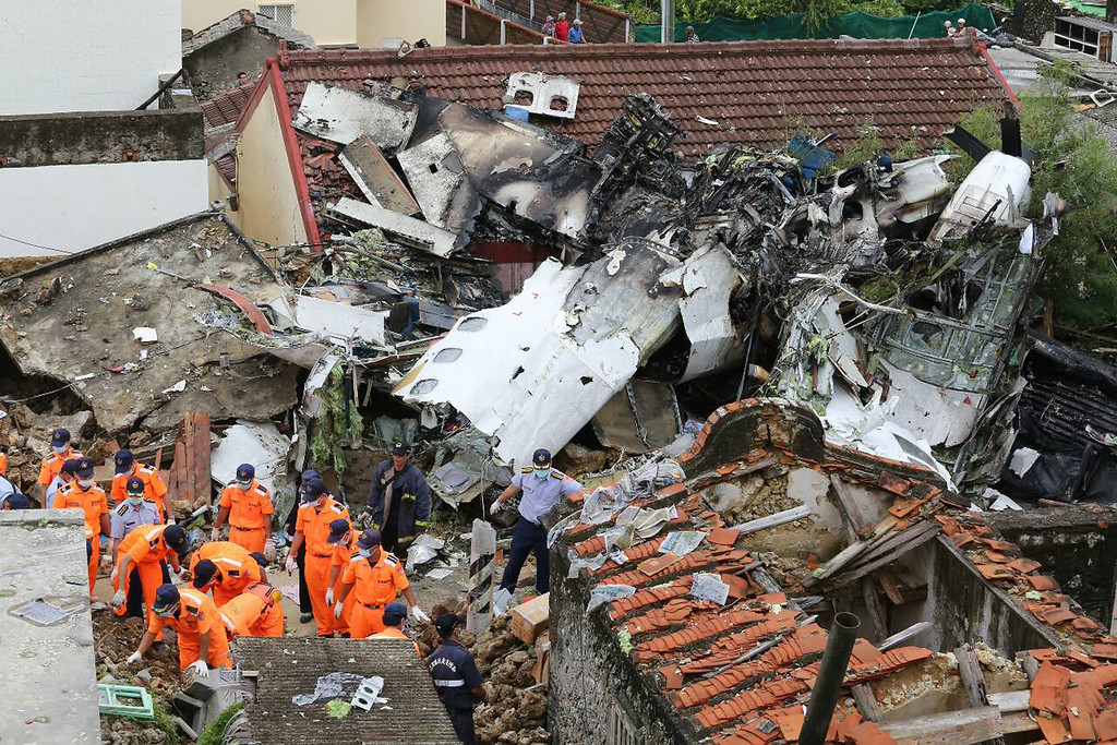 . Rescue workers survey the wreckage of TransAsia Airways Flight GE222 which crashed on the Taiwanese island of Penghu Thursday, July 24, 2014.  (AP Photo)