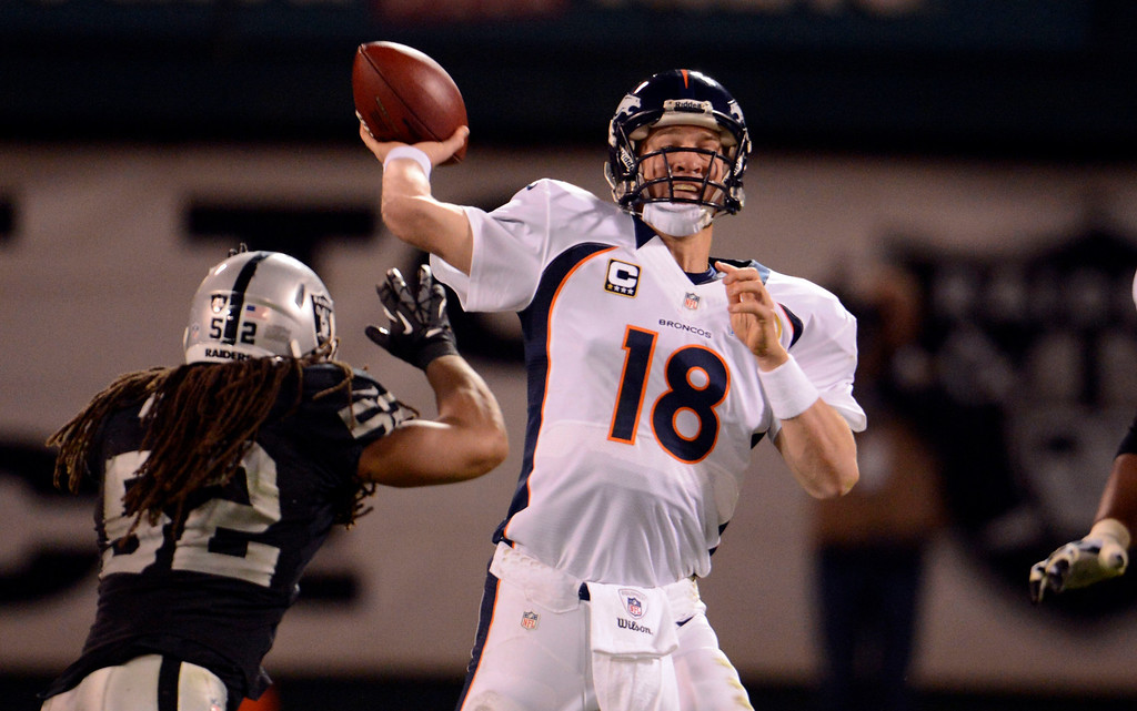 . Oakland Raiders outside linebacker Philip Wheeler (52) puts a big rush on Denver Broncos quarterback Peyton Manning (18) during the fourth quarter Thursday, December 6, 2012 during Thursday Night Football at O.c Coliseum in Oakland  John Leyba, The Denver Post