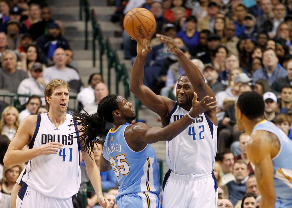 . Dallas Mavericks forward Elton Brand (2nd R) clears a rebound as Denver Nuggets forward Kenneth Faried (2nd L) defends, and Mavericks forward Dirk Nowitzki watches, during the first half of their NBA basketball game in Dallas, Texas, December 28, 2012.  REUTERS/Mike Stone