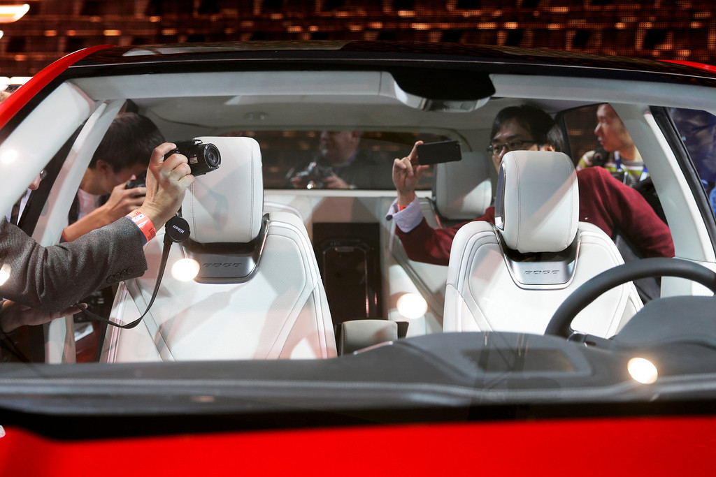 . People photograph the interior of the new Ford Edge concept vehicle at the Los Angeles Auto Show on Wednesday, Nov. 20, 2013, in Los Angeles. (AP Photo/Jae C. Hong)