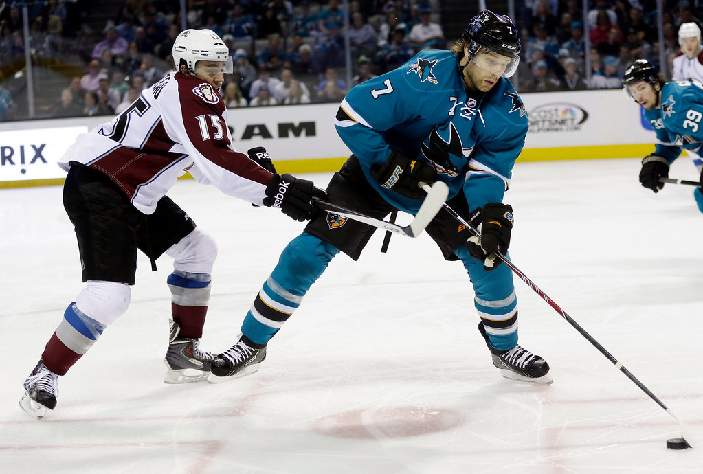 . San Jose Sharks\' Brad Stuart (7) controls the puck next to Colorado Avalanche\'s P.A. Parenteau (15) during the second period of an NHL hockey game on Friday, April 11, 2014, in San Jose, Calif. (AP Photo/Marcio Jose Sanchez)