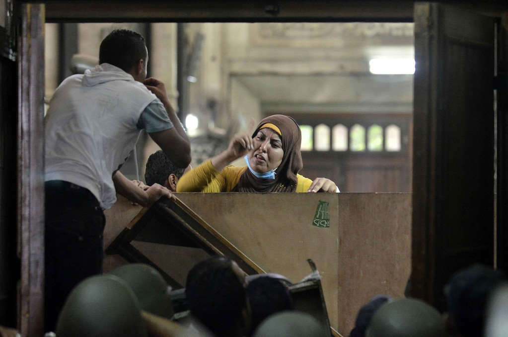 . An Egyptian woman talks to policemen from the inside of Cairo\'s Al-Fath mosque where Islamist supporters of ousted president Mohamed Morsi hole up on August 17, 2013. The standoff at al-Fath mosque in central Ramses Square began on August 16, with security forces surrounding the building where Islamists were sheltering and trying to convince them to leave. MOHAMED EL-SHAHED/AFP/Getty Images