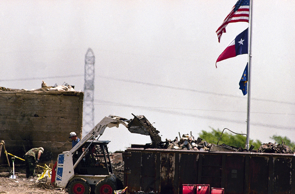 . Investigators clear debris in front of the blockhouse at the destroyed Branch Davidian compound in Waco, Texas on April 26, 1993. Visible in the dumpster are a number of cans. Authorities have expressed health concerns due to rotting food and human remains at the site. (AP Photo/Ron Heflin)