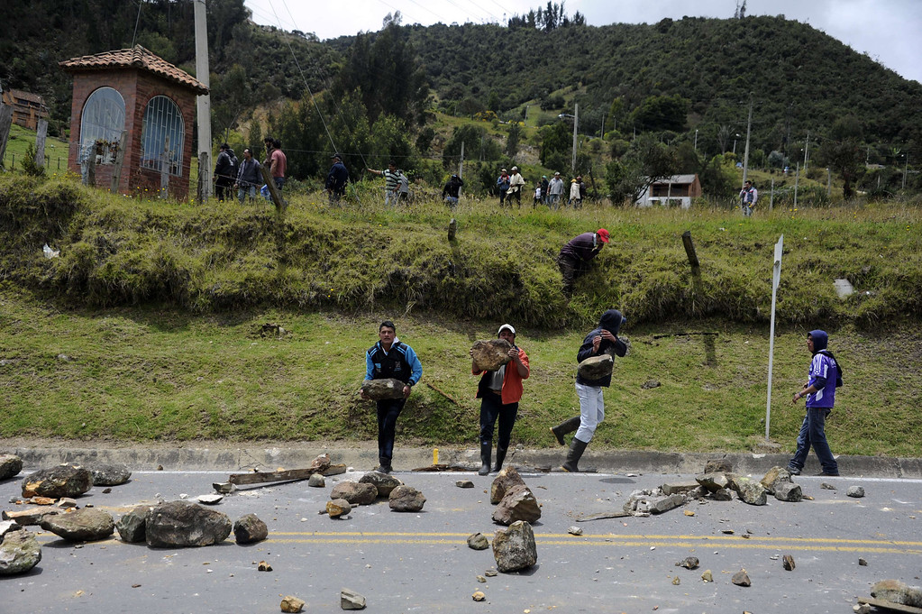. Colombian farmers demanding government subsidies and greater access to land block the road in La Calera, Cundinamarca department, on August 23, 2013. A five-day-old farmworkers\' protest in Colombia claimed its first fatality Friday when a man on a motorcycle crashed and died at a roadblock, police said Friday. Since the protests began Monday, farmworkers have closed roads at dozens of points in across the country, blocking the passage of cargo trucks and other vehicles from makeshift camps erected on sides of roads. EITAN ABRAMOVICH/AFP/Getty Images