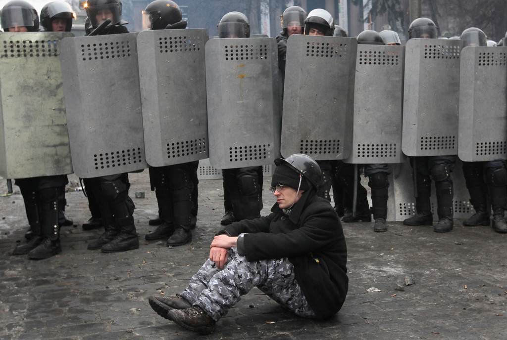 . A pro-European Union activist sits on the ground in front of police in central Kiev, Ukraine, Tuesday, Jan. 21, 2014.  (AP Photo/Sergei Chuzavkov)