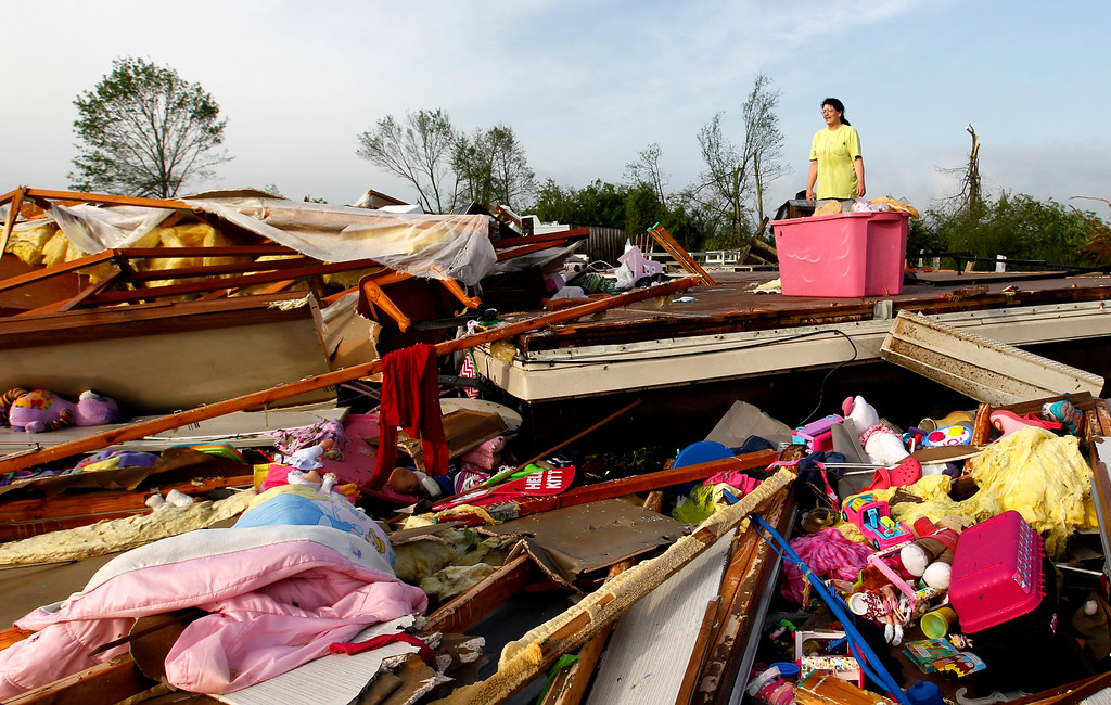 . Teresa Ingram looks for belongings in the debris after a tornado passed through destroying Billy Barbs mobile home park on Tuesday, April 29, 2014, in Athens, Ala.  (AP Photo/Butch Dill)