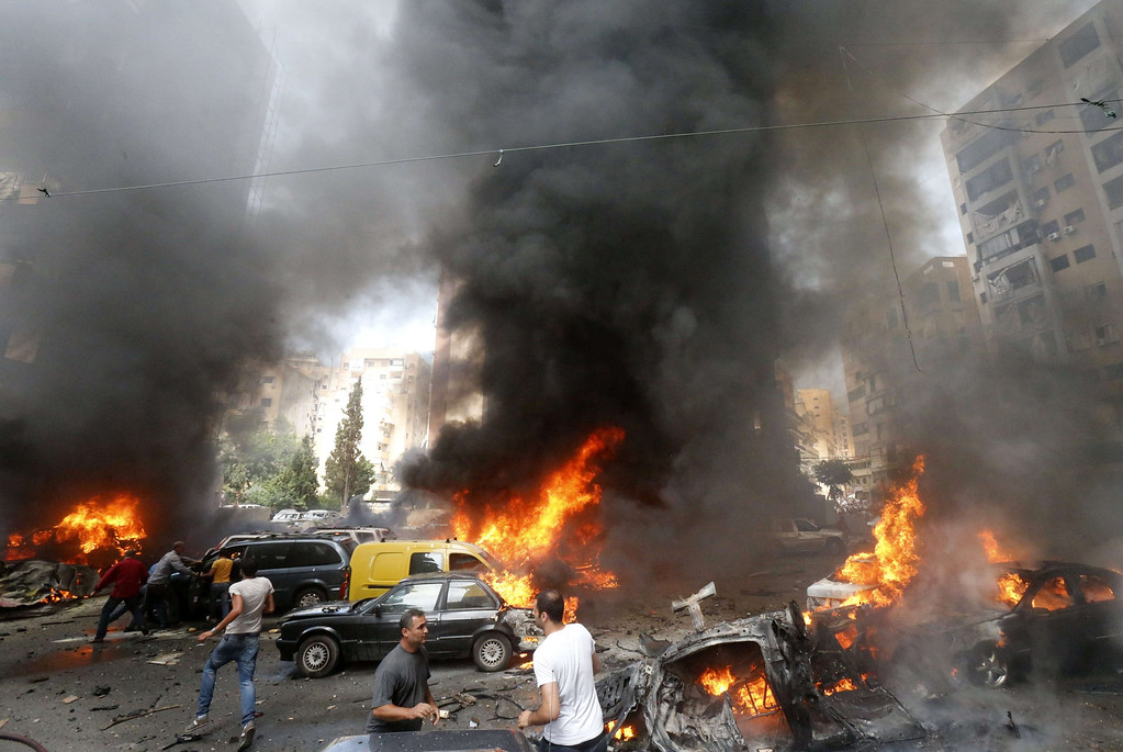 . Civilians gather at the of an explosion in Beirut\'s southern suburb neighbourhood of Bir al-Abed on July 9, 2013.  AFP PHOTO/STR-/AFP/Getty Images
