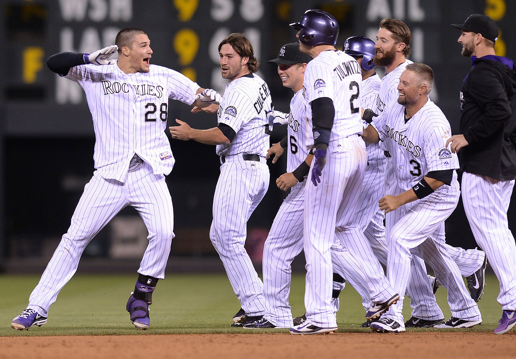 . Nolan Arenado (28) celebrated with teammates after he doubled to drive in two runs in the bottom of the ninth inning to win the game. The Colorado Rockies defeated the San Francisco Giants 5-4 at Coors Field Tuesday night, May 20, 2014. (Photo by Karl Gehring/The Denver Post)