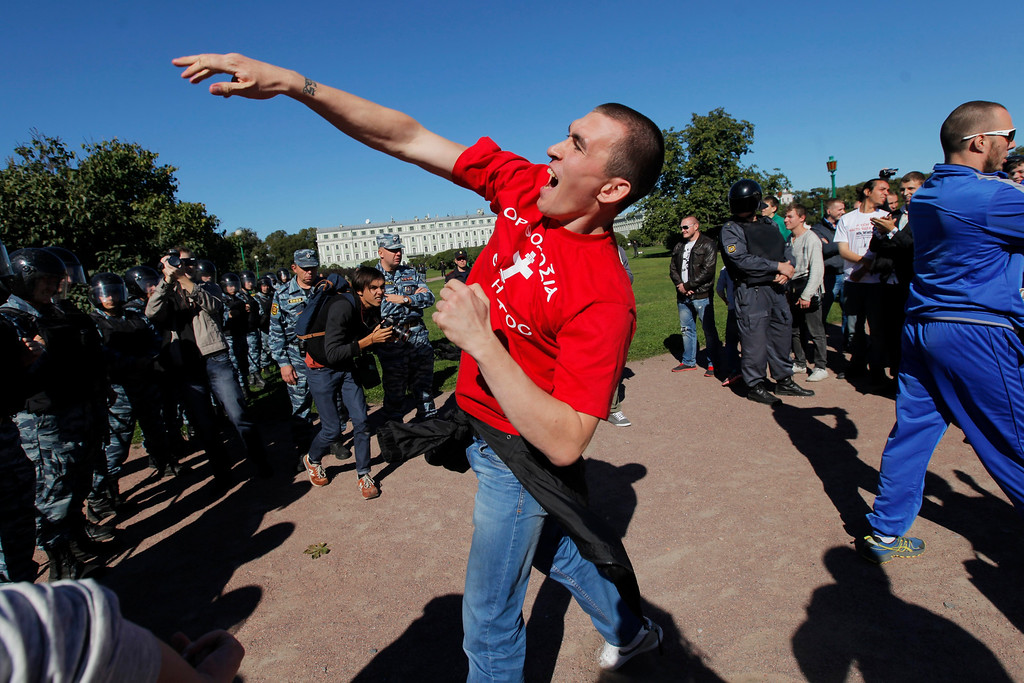 ". An anti-gay demonstrator throws coins at activists protesting law on gay ""propaganda\"" in St.Petersburg, Russia, Friday, Sept. 6, 2013. About two dozen activists have rallied in St. Petersburg to protest a new Russian law banning gay \""propaganda\"" and attract attention of the leaders of the world\'s 20 leading economies. The rally went on peacefully under the close watch of several hundred riot police, who separated the protesters from a few dozen anti-gay demonstrators. (AP Photo/Elena Ignatyeva)"