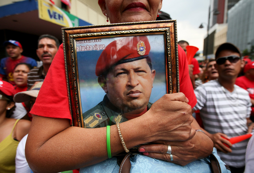 . A supporter of Venezuela\'s newly sworn-in President Nicolas Maduro holds a picture of late President Hugo Chavez during Maduro\'s inauguration in Caracas, Venezuela, Friday, April 19, 2013. The crowds were smaller and more subdued than those that turned out for Chavez, and the opposition boycotted Maduro\'s swearing-in, hoping that the ruling party\'s last-minute decision to allow an audit of nearly half the vote could change the result in a the bitterly disputed presidential election. (AP Photo/Gil Montano)