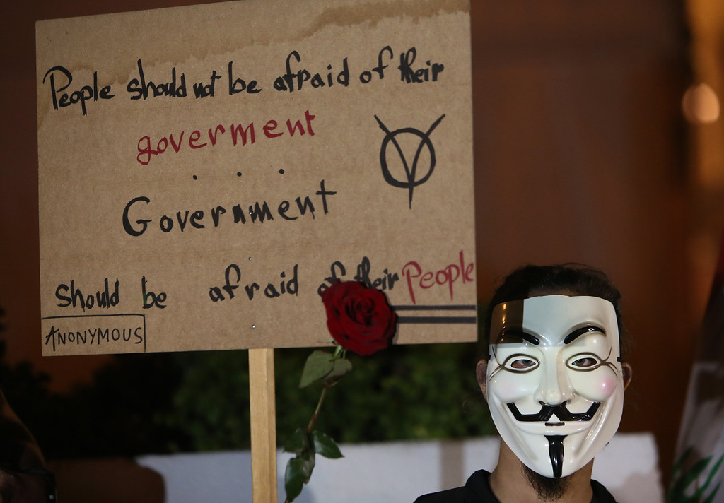 . A Lebanese activist wears a mask and holds up a placard, as he protests against corrupt governments and corporations, in support of the anonymous activist moment, at the Martyrs square, in downtown Beirut, Lebanon, Tuesday, Nov 5, 2013, as part of a Million Mask March of similar rallies around the world on Guy Fawkes Day. (AP Photo/Hussein Malla)