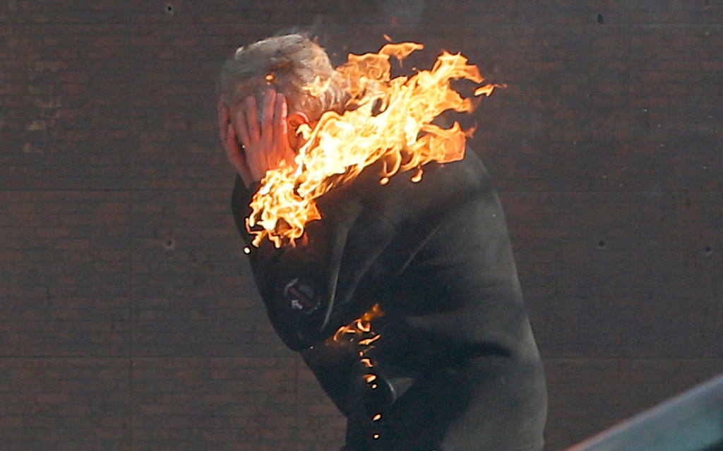. An anti-government protester is engulfed in flames during clashes with riot police outside Ukraine\'s parliament in Kiev, Ukraine, Tuesday, Feb. 18, 2014. (AP Photo/Efrem Lukatsky)