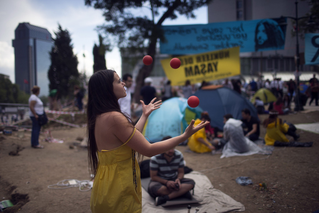 . ISTANBUL, TURKEY - JUNE 06:  A woman juggles as protestors spend their day at Gezi Park in Taksim Square on June 6, 2013 in Istanbul, Turkey. The protests began initially over the fate of Taksim Gezi Park, one of the last significant green spaces in the center of the city. The heavy-handed response of the police, Prime Minister Recep Tayyip Erdogan and his government\'s increasingly authoritarian agenda has broadened the rage of the clashes.  (Photo by Uriel Sinai/Getty Images)