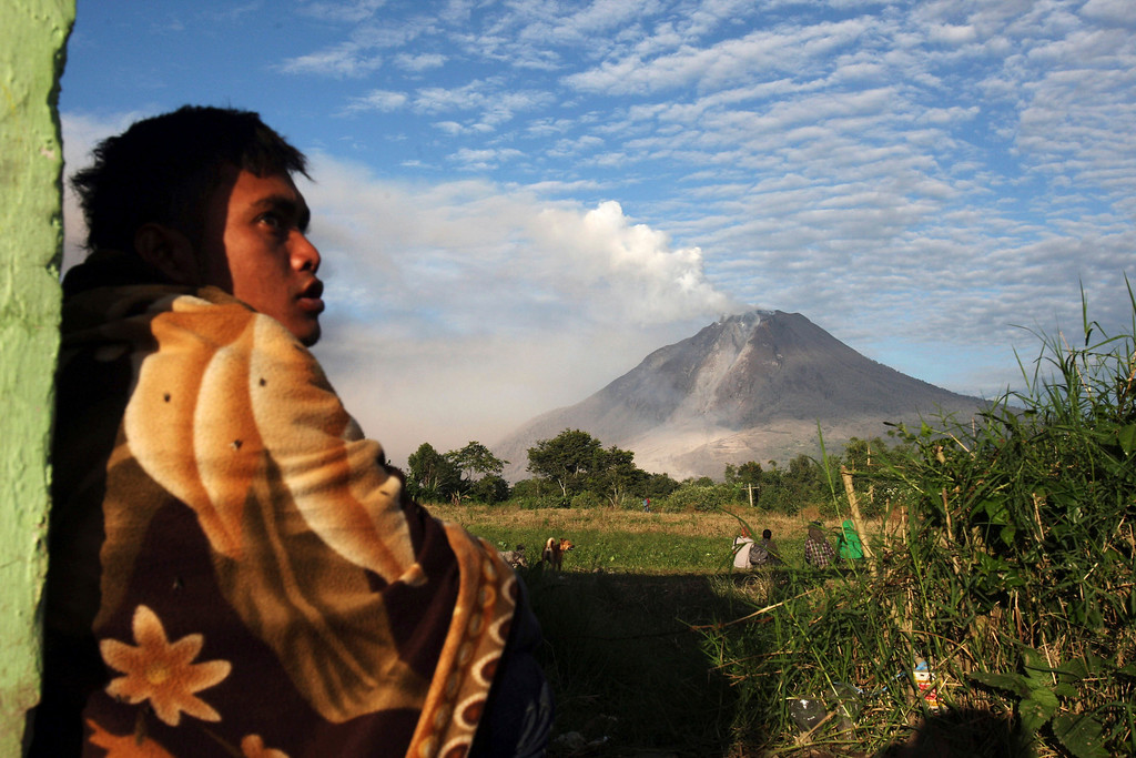 . An Indonesian man watches Mount Sinabung spewing volcanic smoke in Perteguhan, North Sumatra, Indonesia, Monday, Jan. 6, 2014. The 2,600-meter (8,530-foot) volcano has sporadically erupted since September. Authorities extended a danger zone around a rumbling volcano in western Indonesia on Sunday after it spewed blistering gas farther than expected, sending panicked residents streaming down the sides of the mountain. (AP Photo/Binsar Bakkara)