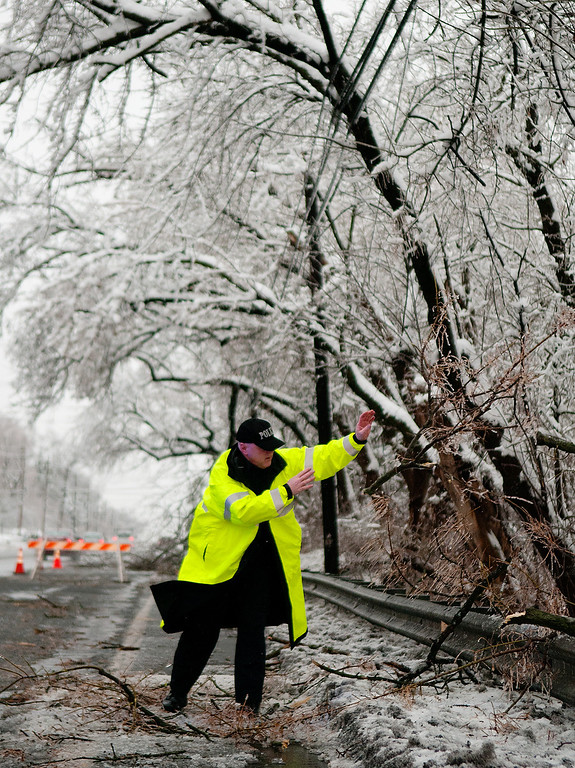 . Warminster police officer clears tree limbs Wednesday morning, Feb. 5, 2014, in Warminster, Pa. Wednesday knocked out power to more than 560,000 electric customers in eastern and central Pennsylvania and prompted school closures, legislative delays and speed reductions on major roadways. (AP Photo/Bucks County Courier Times, Bill Fraser)