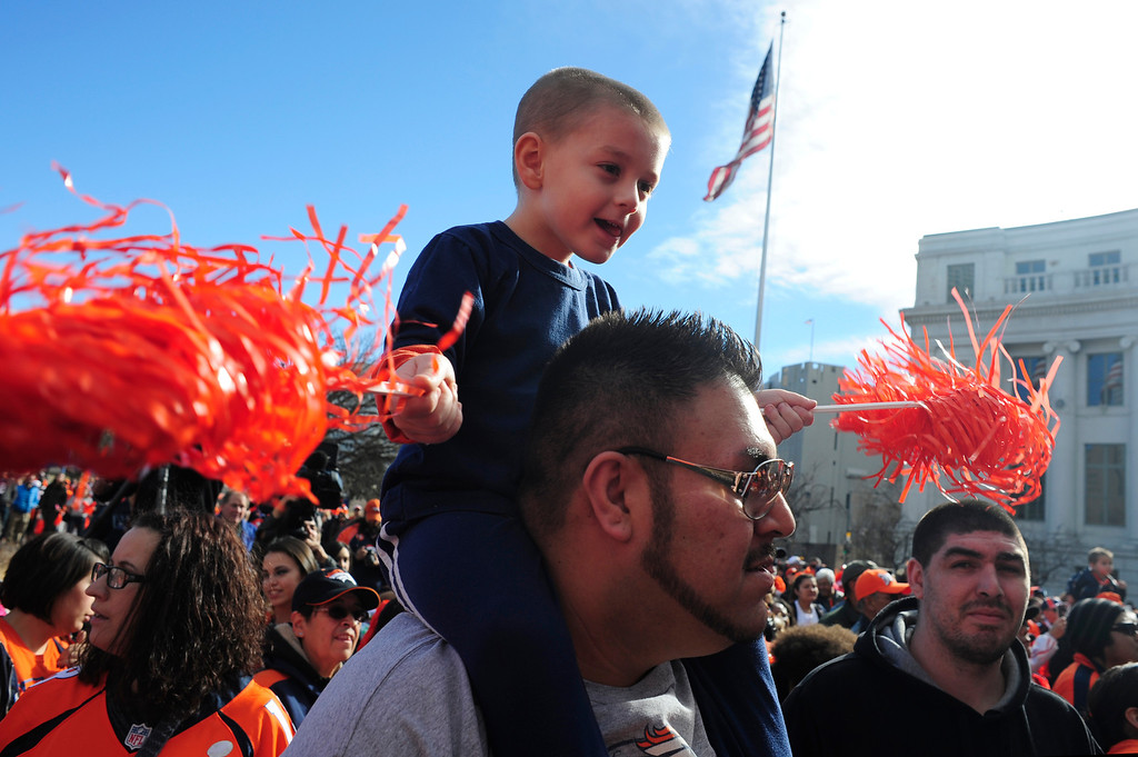 . Justice Marquez, 4, sits atop his uncle, Michael Marquez, during a rally to send off the team, at the City and County Building in Denver, Colorado, Sunday, January 26, 2014. The noon rally brought out scores of supporters and included an appearance by Governor John Hickenlooper and Denver Mayor Michael Hancock.  (Photo By Brenden Neville / Special to The Denver Post)