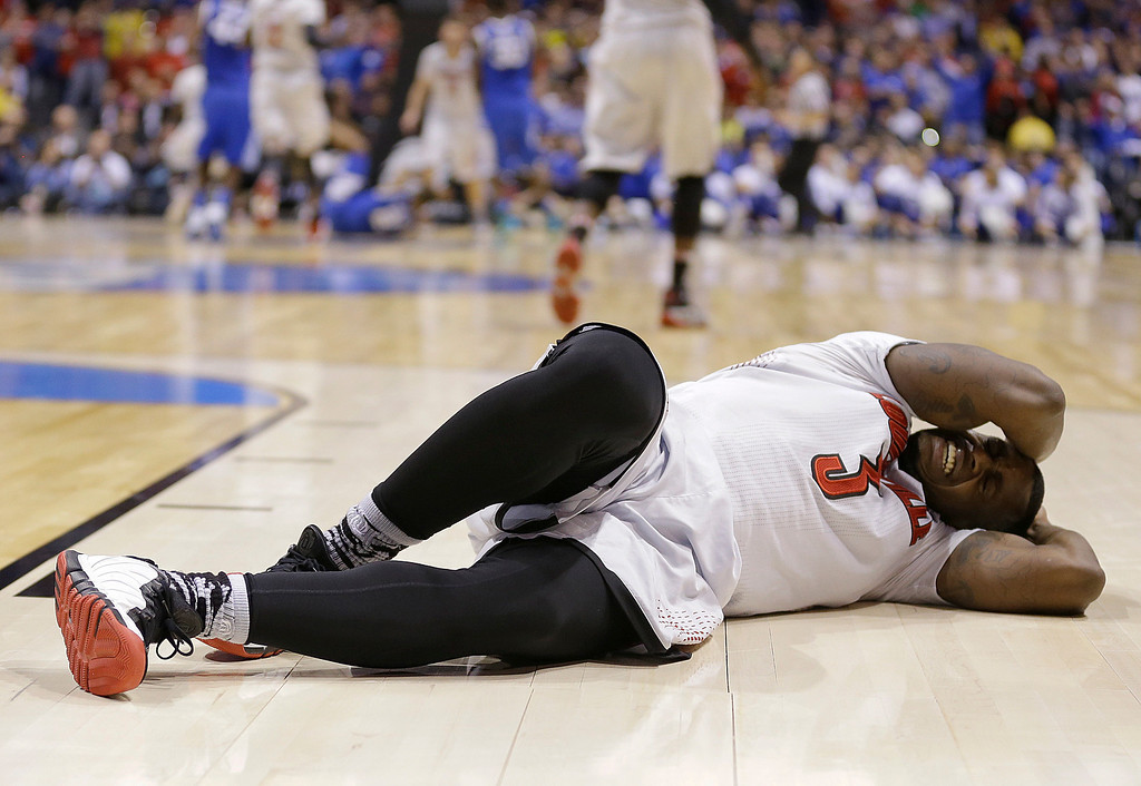 . Louisville\'s Chris Jones reacts after landing hard during the second half of an NCAA Midwest Regional semifinal college basketball tournament game against the Kentucky Friday, March 28, 2014, in Indianapolis. (AP Photo/Michael Conroy)