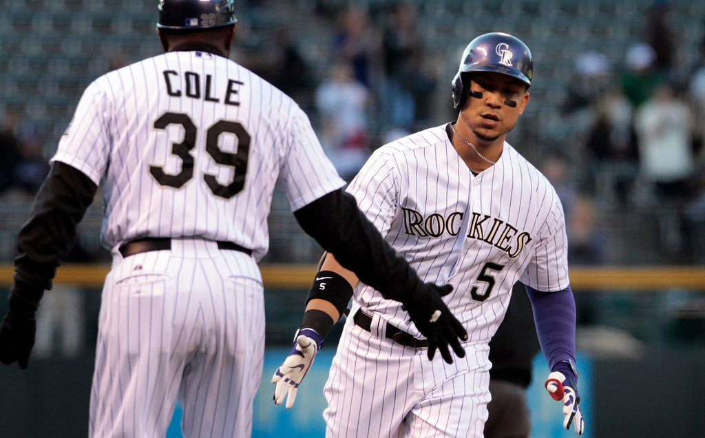 . Colorado Rockies third base coach Stu Cole (39) congratulates Rockies\' Carlos Gonzalez (5) after Gonzalez\'s home run in the first inning of a baseball game against the New York Mets in Denver, Thursday, May 1, 2014.(AP Photo/Joe Mahoney)