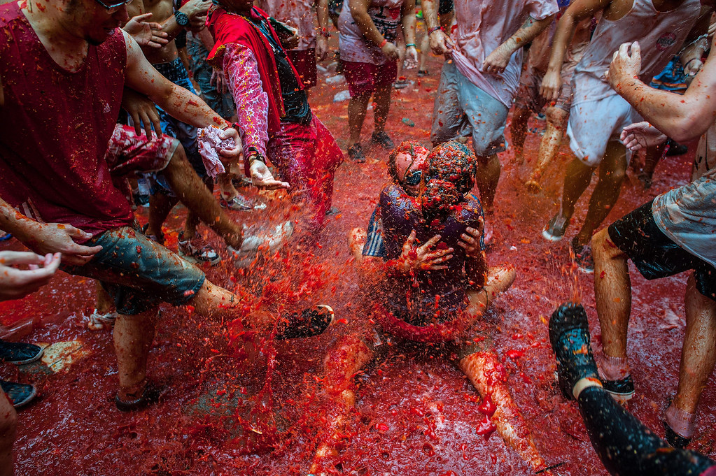 . Two Revelers kiss each other covered in tomato pulp while participating the annual Tomatina festival on August 28, 2013 in Bunol, Spain. An estimated 20,000 people threw 130 tons of ripe tomatoes in the world\'s biggest tomato fight held annually in this Spanish Mediterranean town.  (Photo by David Ramos/Getty Images)