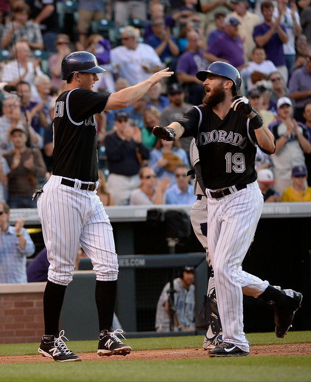 . Colorado Rockies center fielder Charlie Blackmon (19) high fives Colorado Rockies second baseman DJ LeMahieu (9) after his  line drive to right field for a home run  during the third inning against the  San Diego Padres July 8, 2014 at Coors Field. (Photo by John Leyba/The Denver Post)