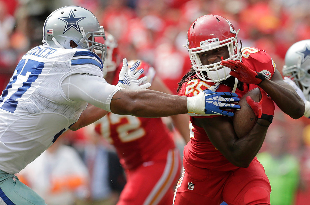 . Kansas City Chiefs running back Jamaal Charles (25) avoids Dallas Cowboys defensive tackle Jason Hatcher (97) during the first half of an NFL football game at Arrowhead Stadium in Kansas City, Mo., Sunday, Sept. 15, 2013. (AP Photo/Charlie Riedel)