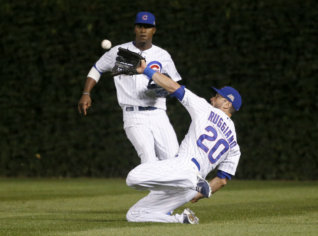 . Chicago Cubs right fielder Justin Ruggiano (20) makes a sliding catch on a ball hit by Colorado Rockies\' Charlie Culberson as center fielder Junior Lake watches during the seventh inning of a baseball game Monday, July 28, 2014, in Chicago. (AP Photo/Charles Rex Arbogast)