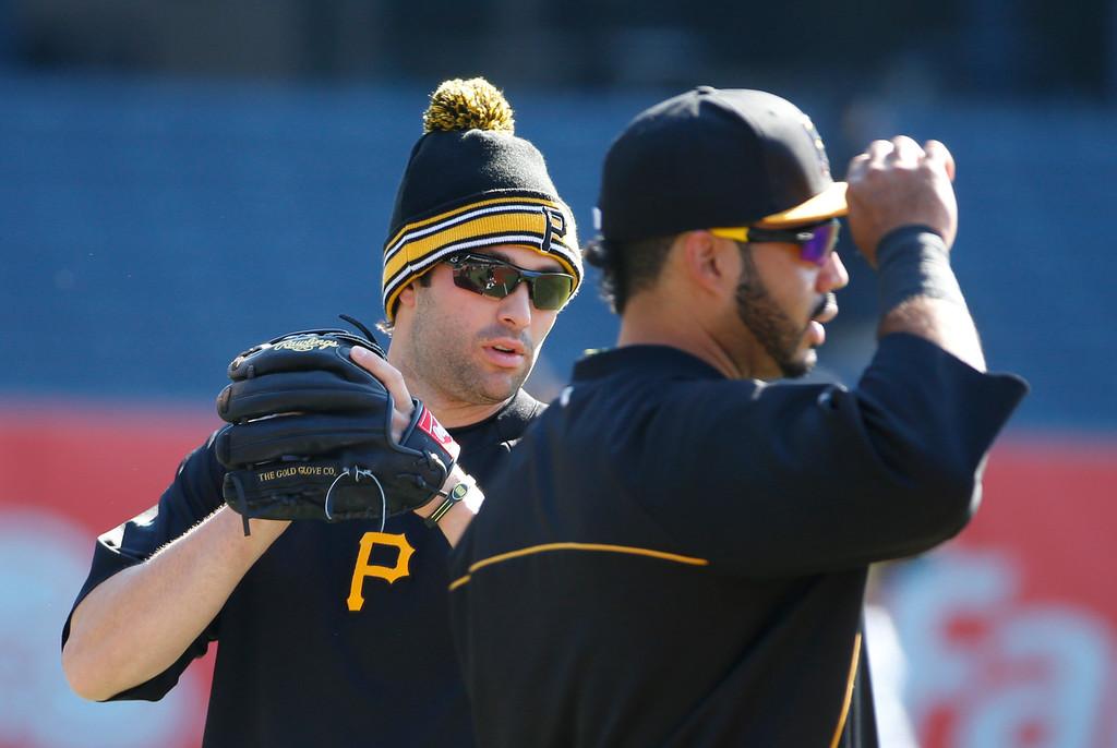 . Pittsburgh Pirates second baseman Neil Walker, left, warms up beside third baseman Pedro Alvarez before their opening day baseball game on Monday, March 31, 2014, in Pittsburgh.  (AP Photo/Gene Puskar)