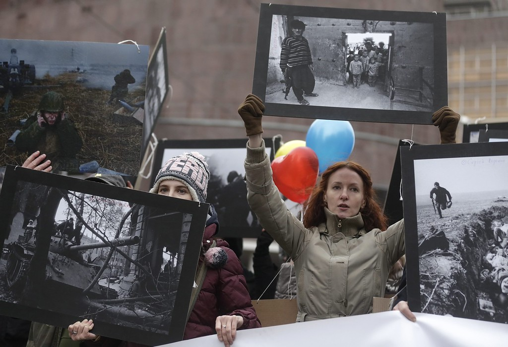 . People hold photos taken at different wars, during an anti-war rally in protest against the Russian military actions in Ukraine, during a demonstration in Moscow, Russia, 15 March 2014. EPA/MAXIM SHIPENKOV