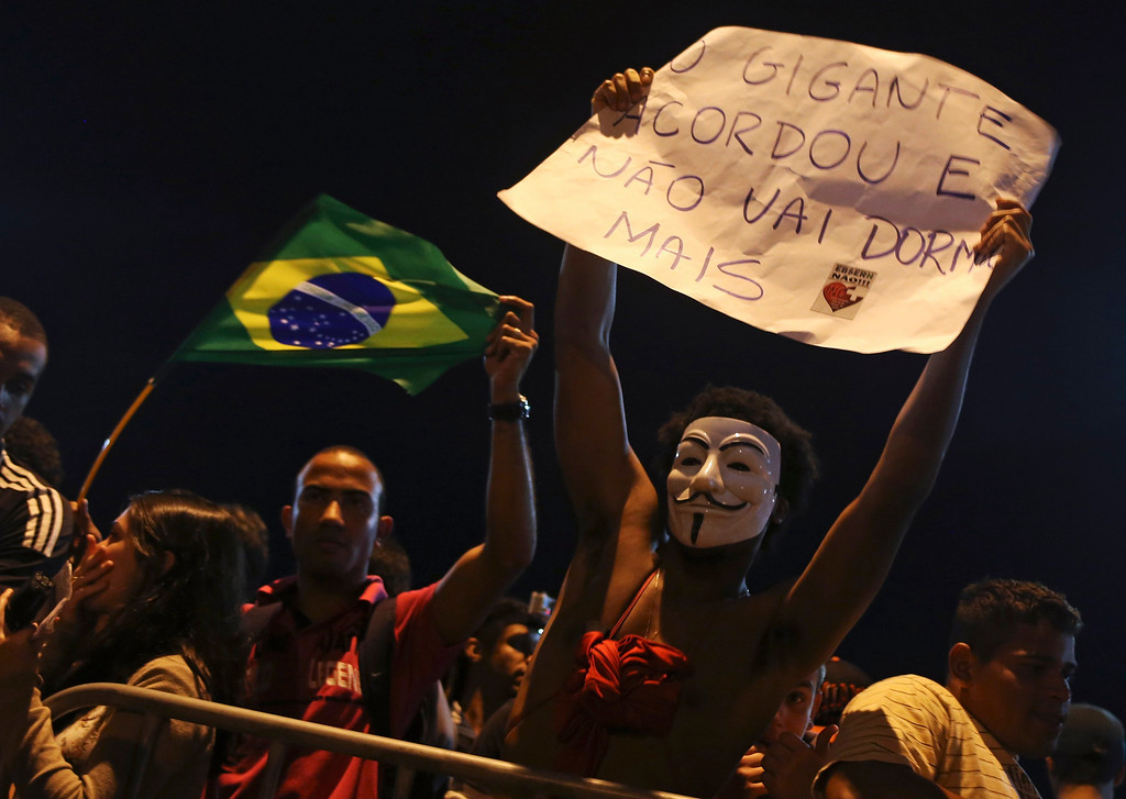 ". A protester wearing a Guy Fawkes mask holds a sign during a protest outside Rio de Janeiro governor Sergio Cabral\'s house, in Rio de Janeiro June 21, 2013.  The sign reads,  ""The giant awakens and he will sleep no more\"". REUTERS/Pilar Olivares"