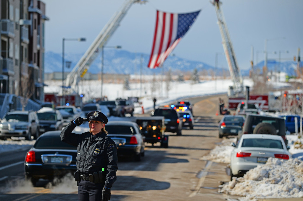 . Broomfield Police Officer Meredith Durham stands in honor during the funeral procession for Jefferson County Sheriff Deputy Sgt. David Baldwin as they leave the First Bank Events Center in Broomfield, February, 03 2014. Baldwin was on motorcycle patrol riding north on Colorado 93 on Sunday morning when he was hit by a vehicle that crossed the double-yellow line. (Photo by RJ Sangosti/The Denver Post)