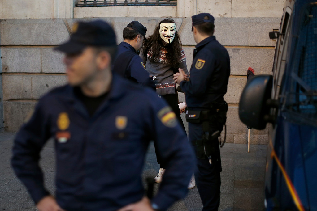 . Police detain a Spanish activist wearing an anonymous mask during a protest against corrupt governments and corporations, in support of the anonymous activist movement, at the Sol square, in Madrid, Spain, Tuesday, Nov 5, 2013, as part of a Million Mask March of similar rallies around the world. (AP Photo/Andres Kudacki)