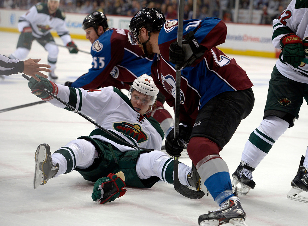 . Mikael Granlund (64) of the Minnesota Wild goes down on a face-off against Marc-Andre Cliche (24) of the Colorado Avalanche during the second period of action. The Colorado Avalanche hosted the Minnesota Wild in the first round of the Stanley Cup Playoffs at the Pepsi Center in Denver, Colorado on Saturday, April 19, 2014. (Photo by John Leyba/The Denver Post)