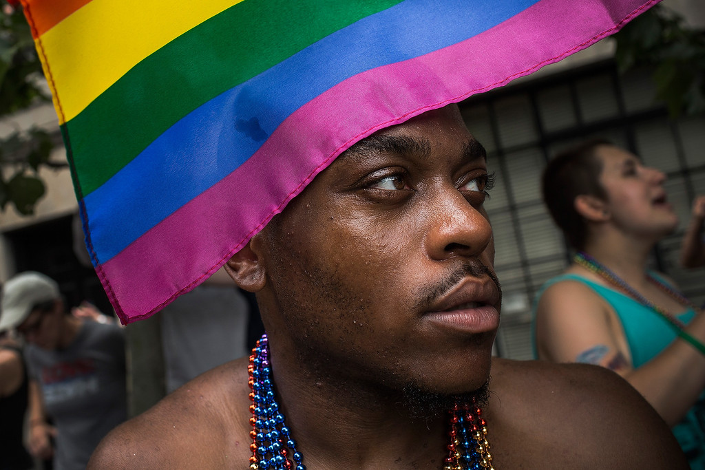 . A reveler watches the New York Gay Pride Parade on June 30, 2013 in New York City.  This year\'s parade was a particularly festive occasion, due to the recent Supreme Court Ruling that it was unconstitutional to ban gay marriage.  (Photo by Andrew Burton/Getty Images)