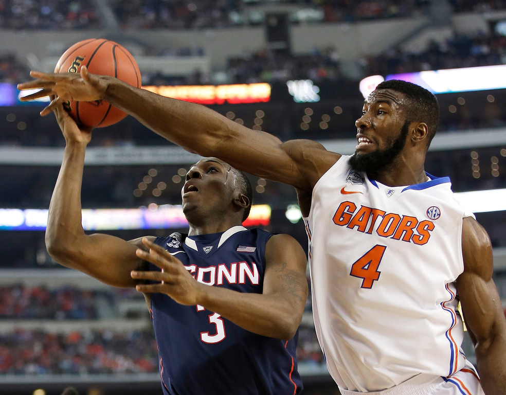 . Connecticut guard Terrence Samuel, left, drives to the basket past Florida center Patric Young during the first half of an NCAA Final Four tournament college basketball semifinal game Saturday, April 5, 2014, in Arlington, Texas. (AP Photo/David J. Phillip)