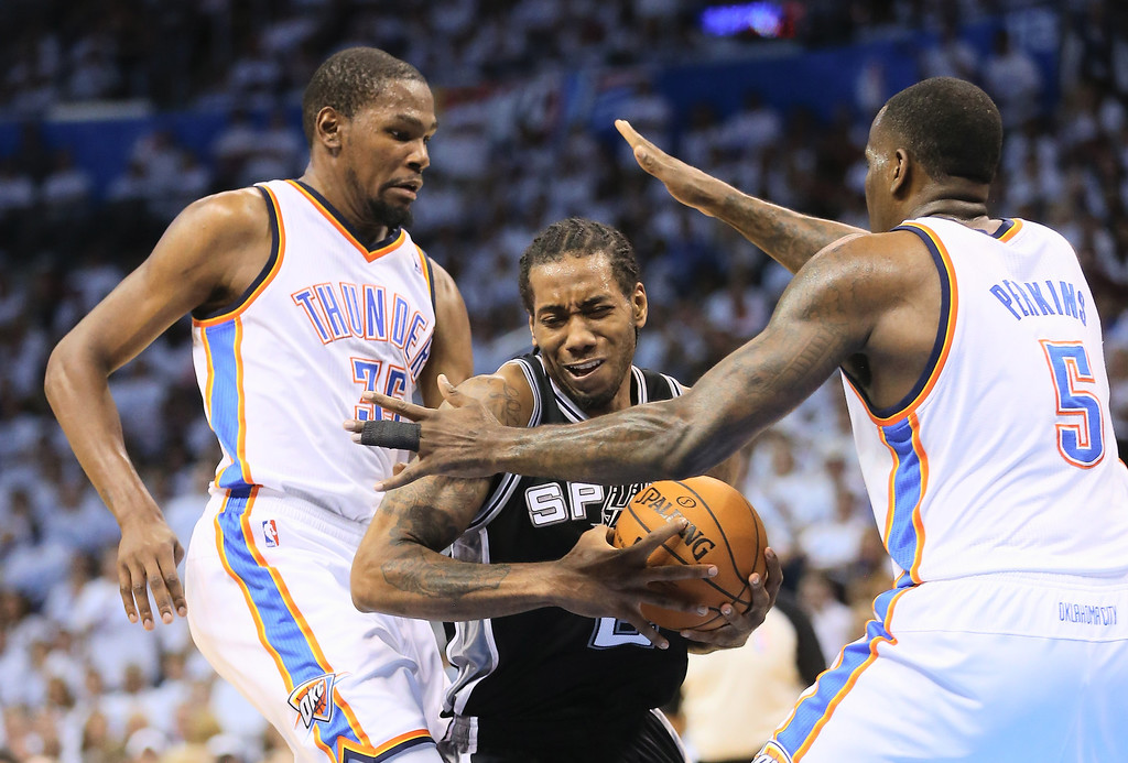 . OKLAHOMA CITY, OK - MAY 31:  Kevin Durant #35 and Kendrick Perkins #5 of the Oklahoma City Thunder defend against Kawhi Leonard #2 of the San Antonio Spurs in the first half during Game Six of the Western Conference Finals of the 2014 NBA Playoffs at Chesapeake Energy Arena on May 31, 2014 in Oklahoma City, Oklahoma. (Photo by Ronald Martinez/Getty Images)