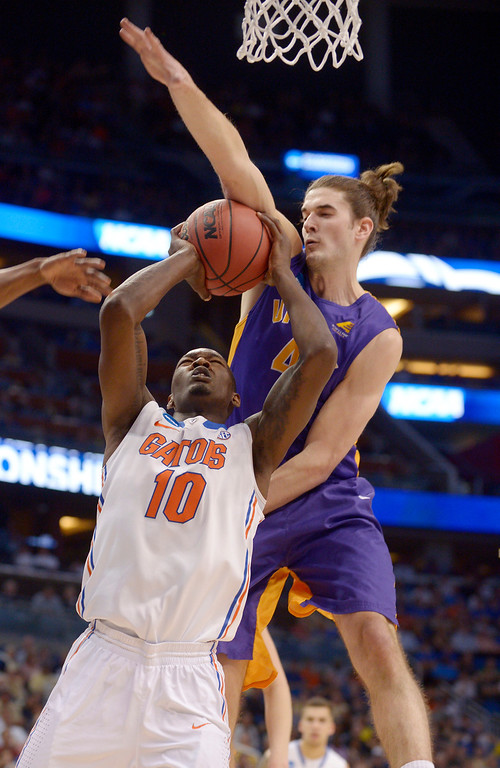 . Albany center John Puk, right, blocks a shot to the basket by Florida forward Dorian Finney-Smith (10) during the first half in a second-round game in the NCAA college basketball tournament Thursday, March 20, 2014, in Orlando, Fla. (AP Photo/Phelan M. Ebenhack)