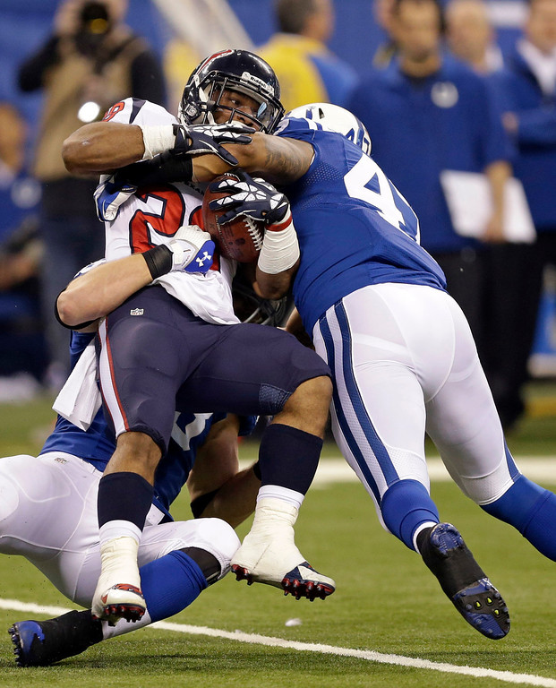 . Indianapolis Colts\' Weslye Saunders, right, tackles Houston Texans\' Dennis Johnson during the second half of an NFL football game in Indianapolis, Sunday, Dec. 15, 2013. (AP Photo/Darron Cummings)