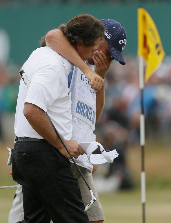 . Phil Mickelson of the United States celebrates after his final putt on the 18th green with his caddie Jim Mackay during the final round of the British Open Golf Championship at Muirfield, Scotland, Sunday July 21, 2013. (AP Photo/Jon Super)