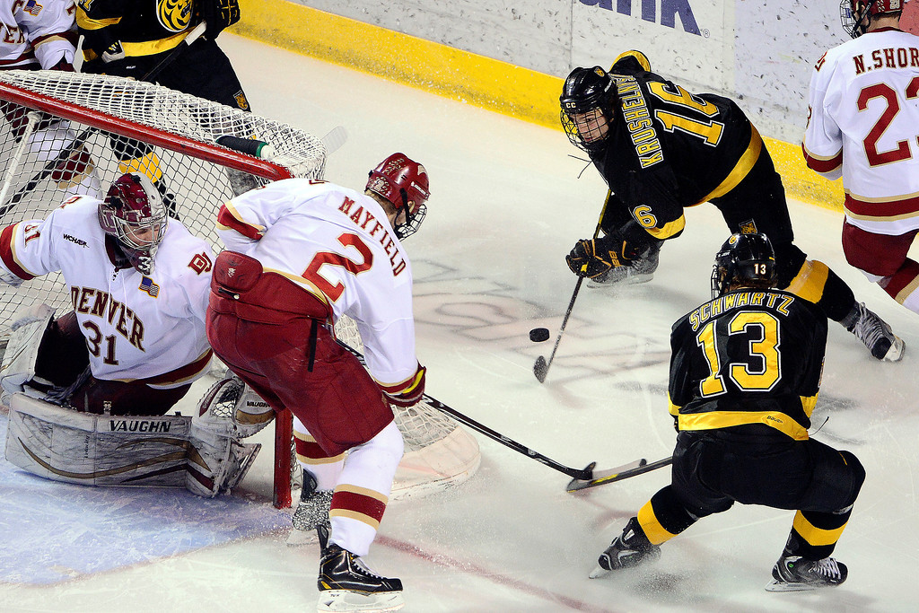 . DENVER, CO - MARCH 17: Alexander Krushelnyski (16) of the Colorado College Tigers controls the puck behind the net against the University of Denver Pioneers during the third period of action. The University of Denver loses 4-3 to Colorado College during the WCHA playoffs at Magness Arena. (Photo by AAron Ontiveroz/The Denver Post)
