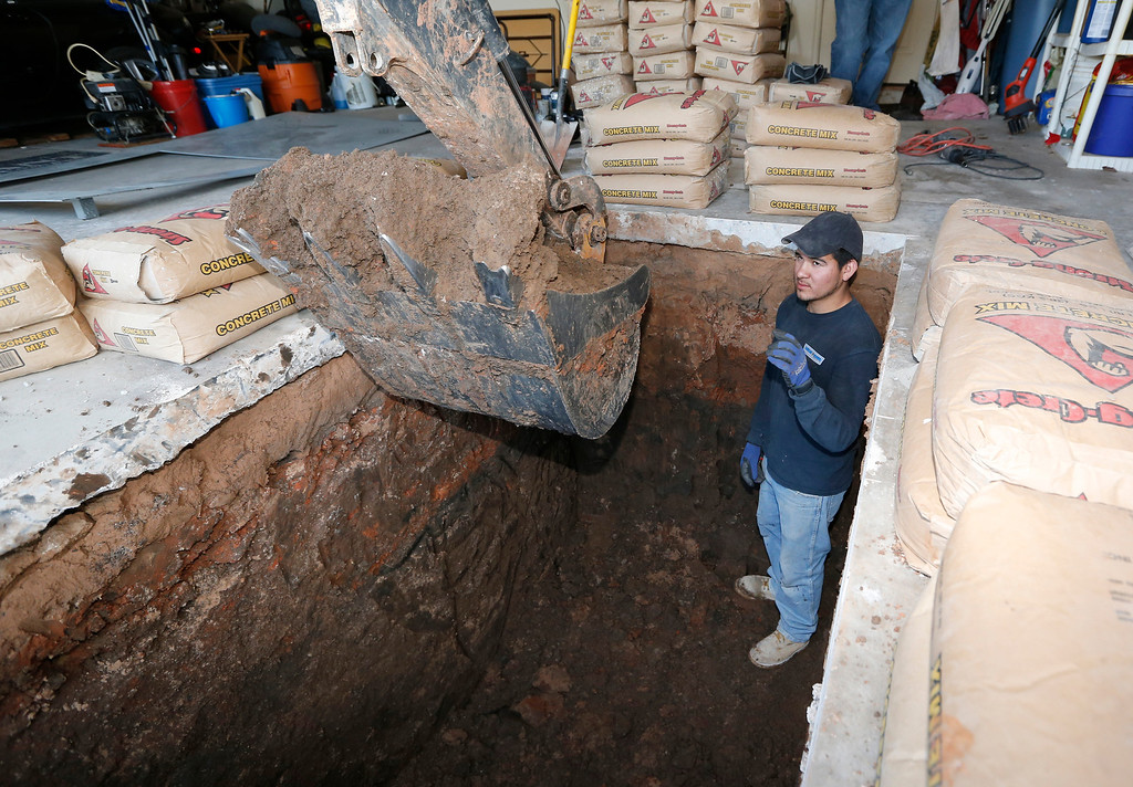 . In this Thursday, May 1, 2014 photo, Jacob Ortiz, of Thunderground Storm Shelters, directs as the finishing touches are put on a hole for a storm shelter installation in the garage of a residence in Oklahoma City.  (AP Photo/Sue Ogrocki)
