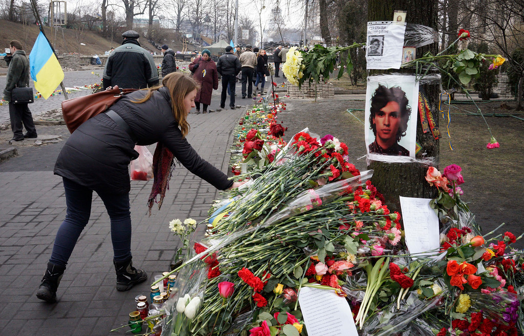 . A woman lays flowers at the spot where a protester was killed in a recent clash with riot police in Kiev\'s Independence Square, Ukraine, Friday, Feb. 28, 2014. Official reports say 82 people were killed in severe clashes between opposition activists and riot police. (AP Photo/Efrem Lukatsky)