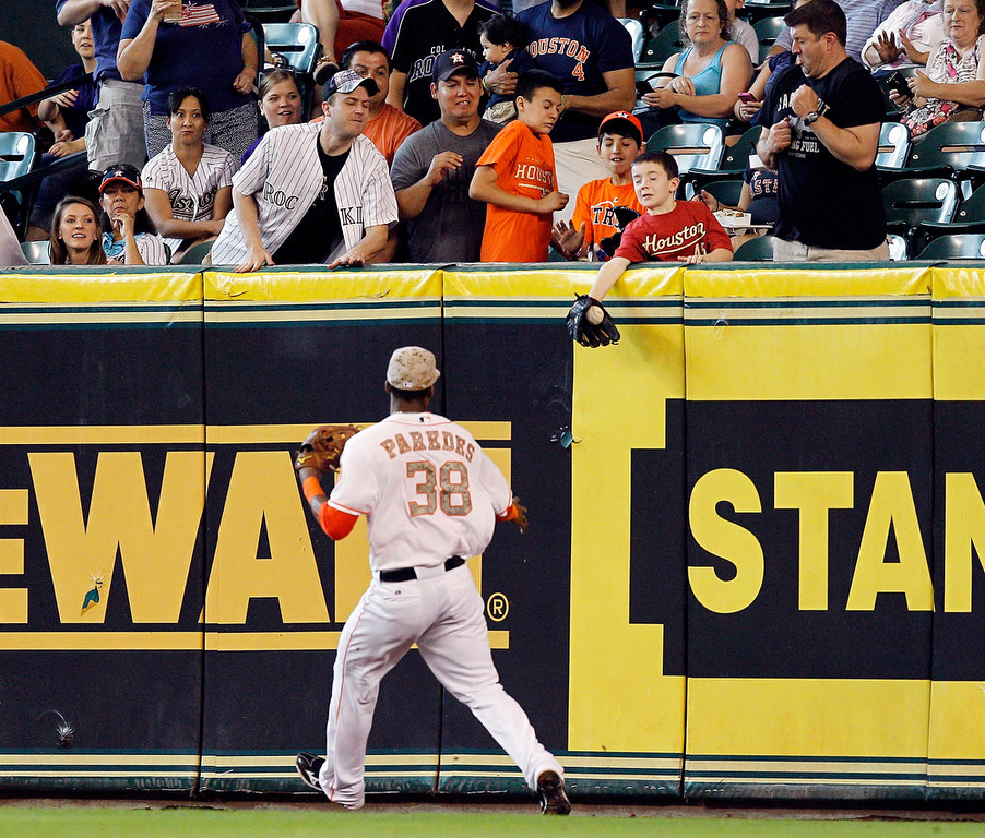 . A young fan reaches for the ball over the  head of Houston Astros right fielder Jimmy Paredes (38) hit by Colorado Rockies left fielder Carlos Gonzalez (5) in the first inning during a baseball game, Monday, May 27, 2013, in Houston. (AP Photo/Bob Levey)