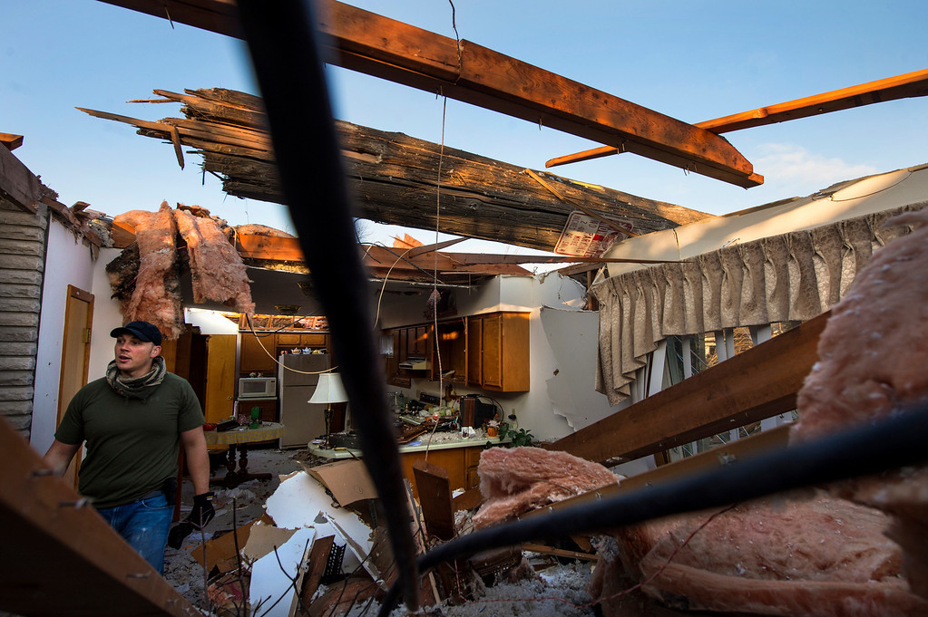 . Dave Look hauls items out of the destroyed home of his grandparents, Louis and Mabel Look, in Pekin, Ill. on Monday, Nov. 18, 2013, a day after a tornado hit the area. Louis and Mabel were in their kitchen when the tornado hit, tearing off the roof and flinging a utility pole in its place.  (AP Photo/Journal Star, Fred Zwicky)