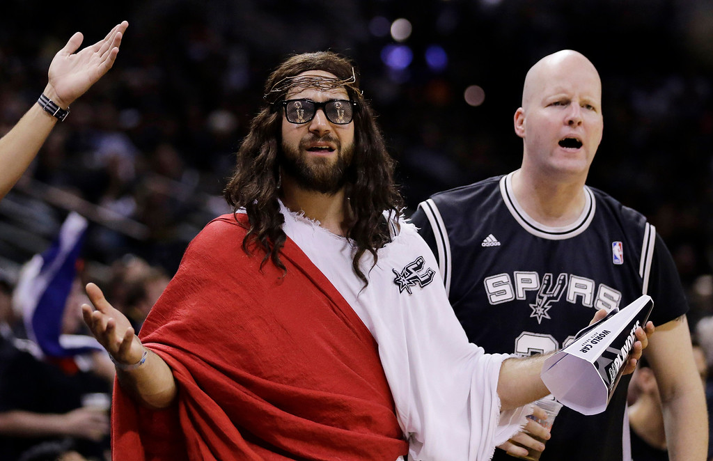 """. Fans, including \""""Spurs Jesus\"""", center, react to a call during the second half in Game 1 of the NBA basketball finals between the San Antonio Spurs and the Miami Heat on Thursday, June 5, 2014 in San Antonio. (AP Photo/Eric Gay)"""