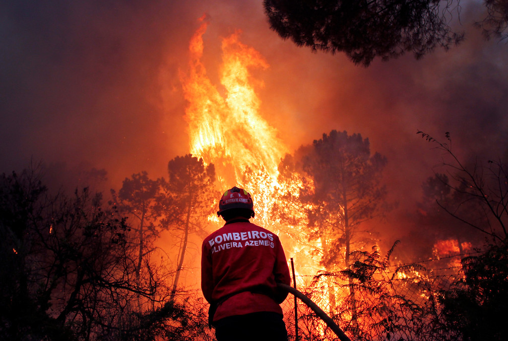 . A Portuguese firefighter works to extinguish a wildfire near Caramulo, north Portugal, Thursday, Aug. 29, 2013. Portuguese officials said a woman firefighter died in a forest blaze, becoming the fifth fatality among emergency crews in a month as summer wildfires scorch large areas of parched countryside. (AP Photo/Francisco Seco)