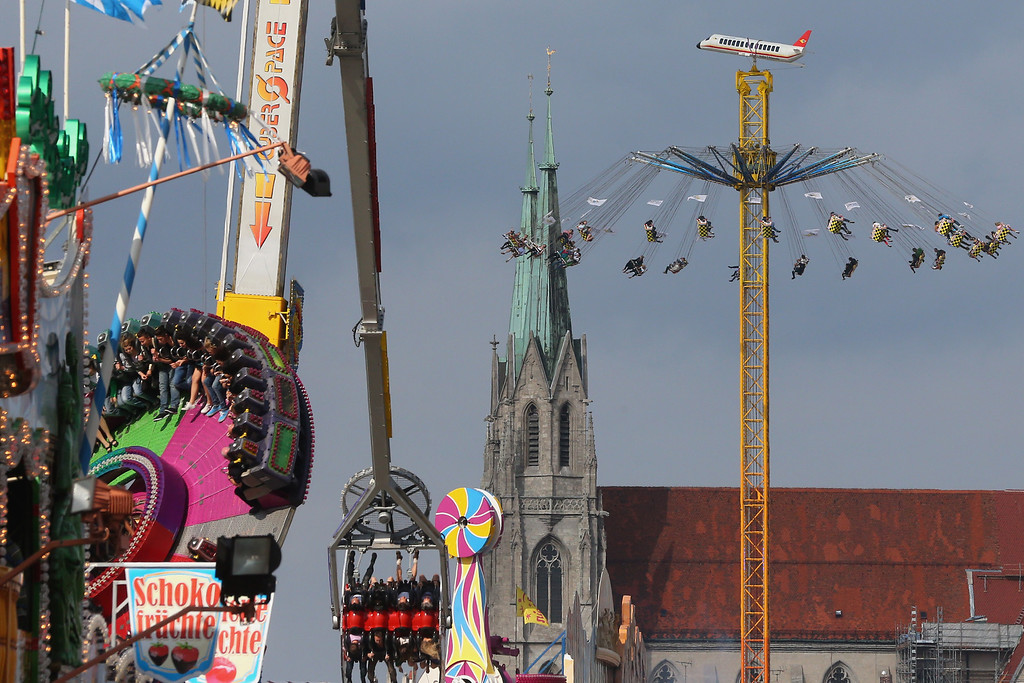 . People enjoy riding on a merry-go-round in front of the Sankt Paul Church Munich at the Oktoberfest on September 21, 2013 in Munich, Germany. The Munich Oktoberfest, which this year will run from September 21 through October 6, is the world\'s largest beer fest and draws millions of visitors.  (Photo by Alexander Hassenstein/Getty Images)