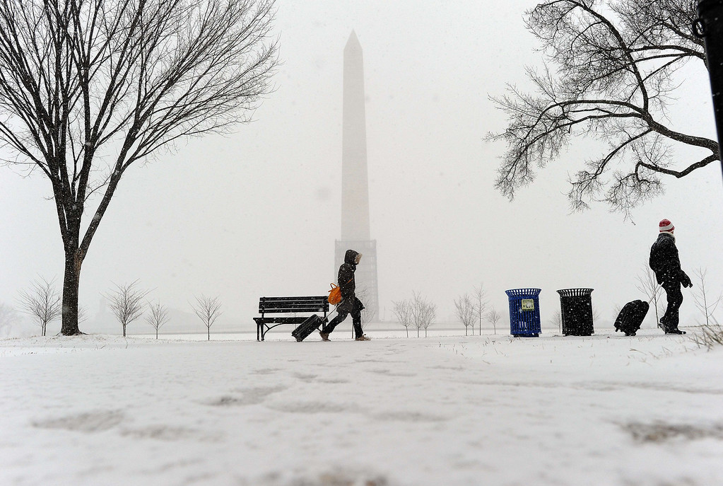 . A couple haul their suitcases as they make their way under a snowfall on January 21, 2014 in Washington, DC. AFP PHOTO/Jewel  SAMAD/AFP/Getty Images